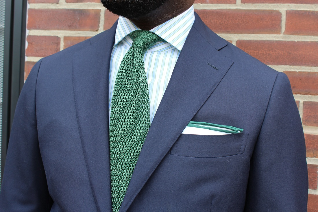 Striped shirt and blue suit green tie